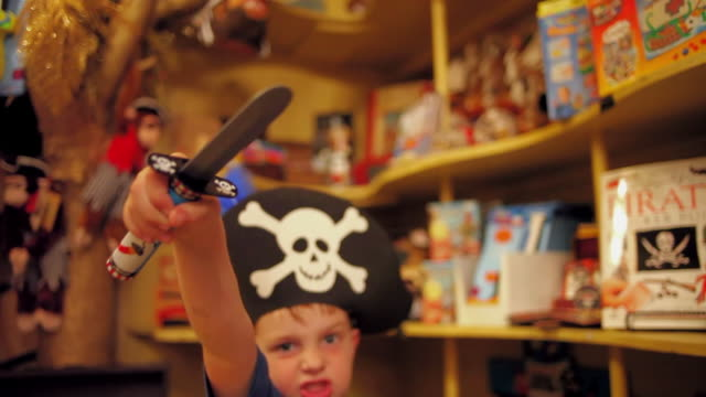 young boy wearing pirate hat holds up toy dagger in toy store - toy store stock videos and b-roll footage