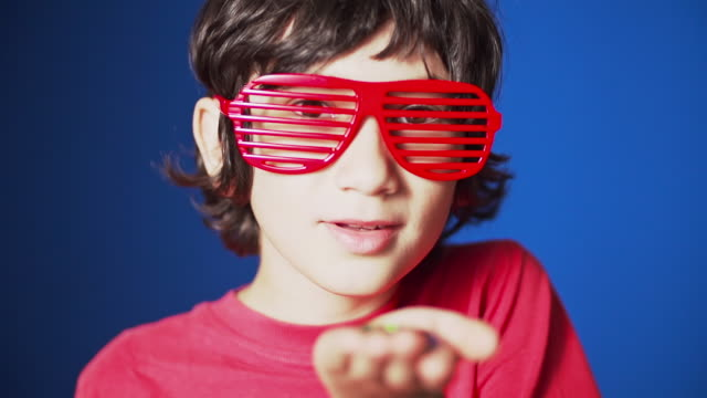 vídeos de stock, filmes e b-roll de cu slo mo r/f young boy wearing sunglasses blowing multicolored sparkly glitter with jumping, dancing and partying / auckland, new zealand  - só um menino adolescente
