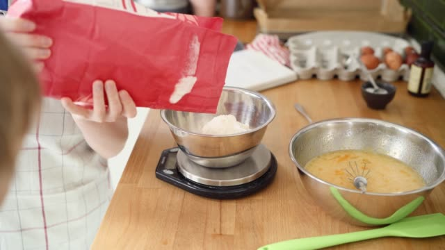a young boy weighing out flour into a bowl - baking stock videos & royalty-free footage
