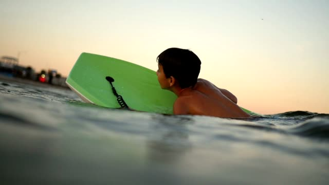 Young boy wipes out while riding a wave on a body board