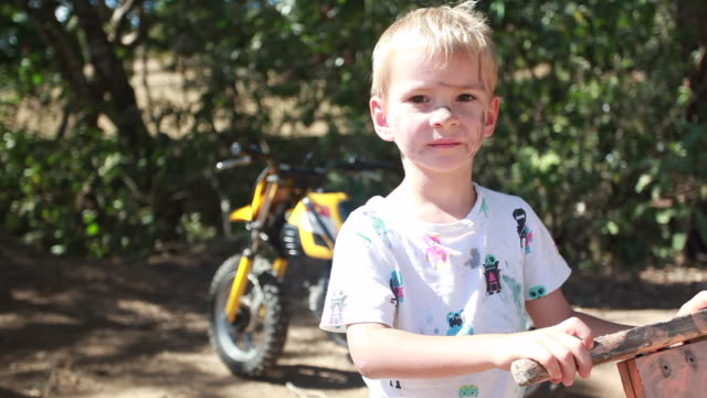 young boy with a dirty face holding wooden bike with a dirt bike parked behind him - kelly mason videos stock-videos und b-roll-filmmaterial