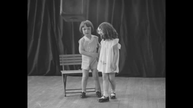 A young boy with a pageboy haircut wearing a onepiece jumpsuit sings and dances on stage with a girl in curls and a pinafore they sit together on a...