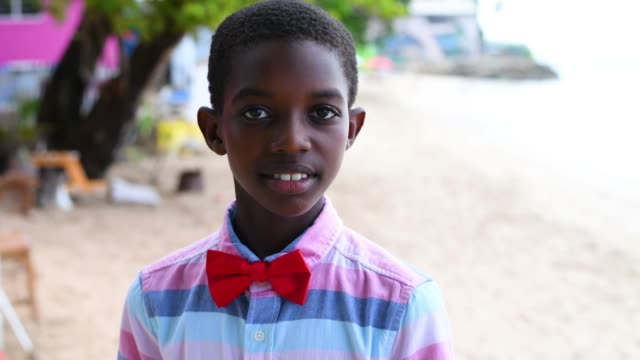 young boy with a red bow tie - karibik stock-videos und b-roll-filmmaterial