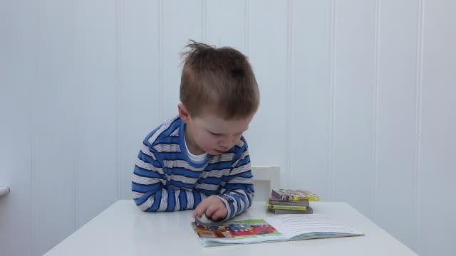 young boy with book - vorschulkind stock-videos und b-roll-filmmaterial