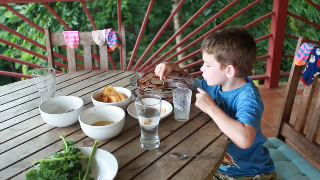 a young boy with chocolate on his face and arm sits at table eating from a big bowl lined with chocolate creating his own concoction of chocolate milk. - kelly mason videos stock videos & royalty-free footage