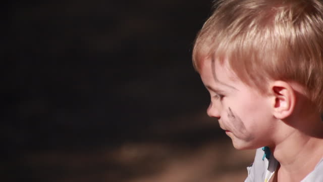 vidéos et rushes de young boy with dirt on his face sitting on a wooden bike on a sunny summer day - kelly mason videos
