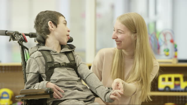 young boy with disability smiles and laughs with caregiver - persons with disabilities stock videos & royalty-free footage
