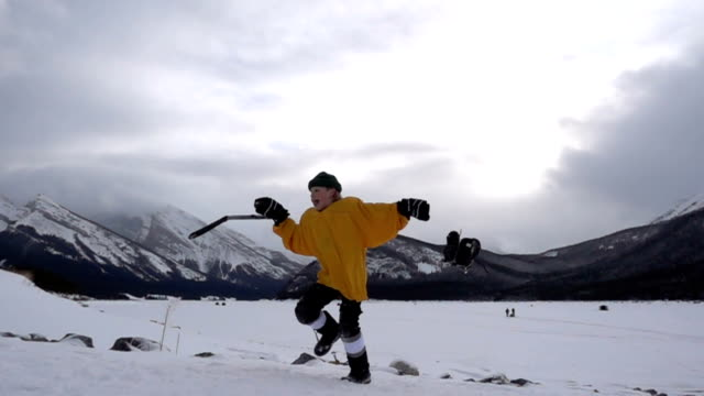 Young boy with hockey equipment having fun in the snow, mountains