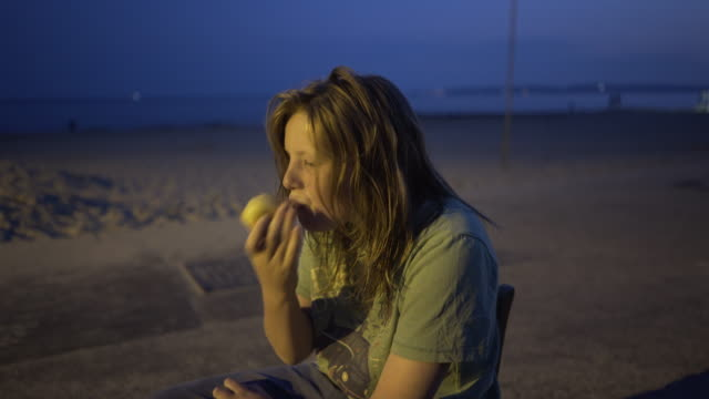 a young boy with long wet hair eating an apple at dusk. - wet hair stock videos & royalty-free footage