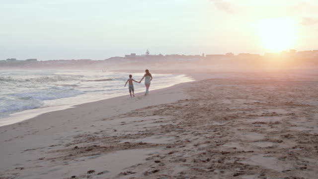 young boy with mother - walking hand in hand and enjoying themselves on a sandy beach during sunset - the joy of motherhood - 40 sekunden oder länger stock-videos und b-roll-filmmaterial