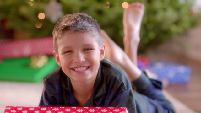 Young boy with present smiles at camera in front of Christmas tree
