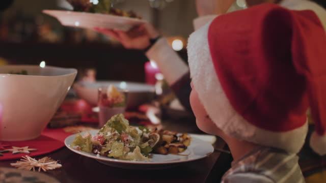 vídeos y material grabado en eventos de stock de young boy with santa hat at christmas dinner table - cena