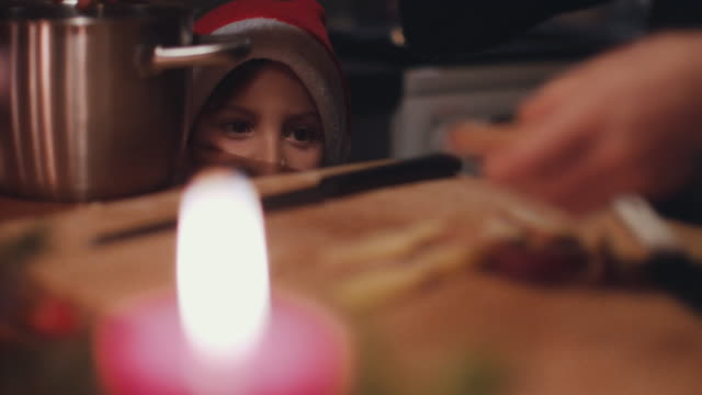 young boy with santa hat watching woman cutting a sweet potato on wooden cutting board - godmother stock videos & royalty-free footage