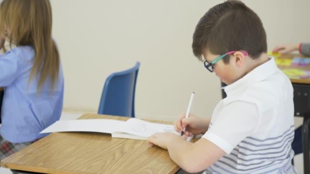 vidéos et rushes de jeune garçon travaillant à son bureau d'école - reprise des cours