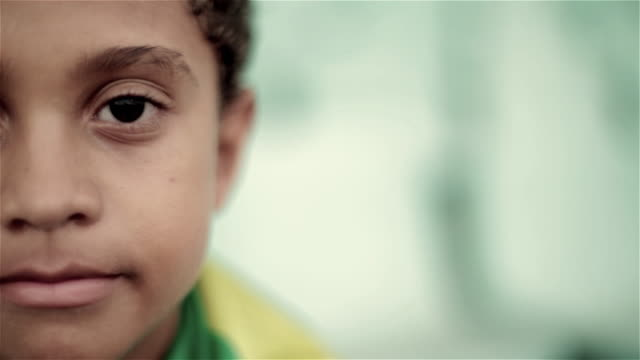 young boy wrapped in brazilian flag stares at camera in soccer stadium - staring stock-videos und b-roll-filmmaterial