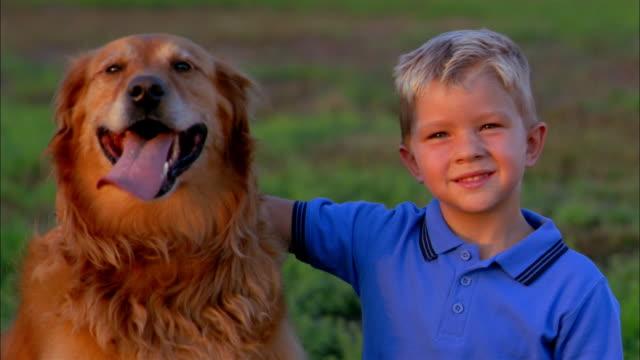 A young boy wraps his arm around a dog's neck.