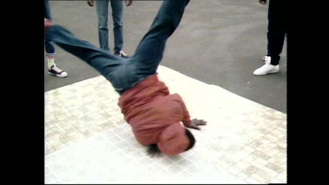 vídeos de stock e filmes b-roll de young boys breakdance on lino in london public park; 1984 - cultura hip hop