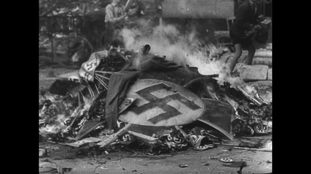 / young boys carry a nazi sign over to a fire for burning / boys throw flag after nazi flag onto the flames / poster of hitler goes up in flames... - 1945 stock-videos und b-roll-filmmaterial