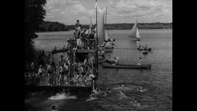 young boys entering camp ws campers standing us flag pole ws girls playing field hockey ws boys wading through water by rock ws boys on pier diving... - field hockey stock videos and b-roll footage
