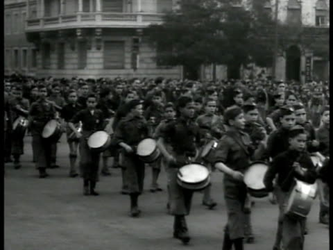 vídeos y material grabado en eventos de stock de young boys marching in parade w/ drums. boys marching w/ flags of portugal coat of arms emblem. pedestrian w/ officer watching. young men & boys... - fascismo