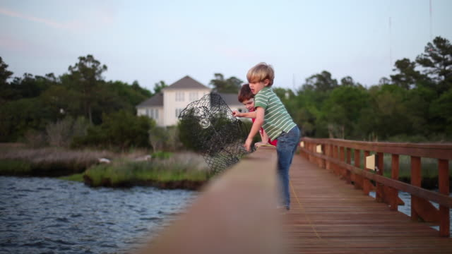 young boys on dock hoist crab-trap and throw it into the river - cast member stock videos & royalty-free footage