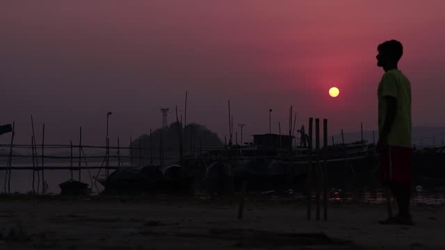 young boys play cricket in the banks of brahmaputra river during sunset, on april 5, 2021 in guwahati, india. cricket is the most popular sport in... - lifestyles stock videos & royalty-free footage