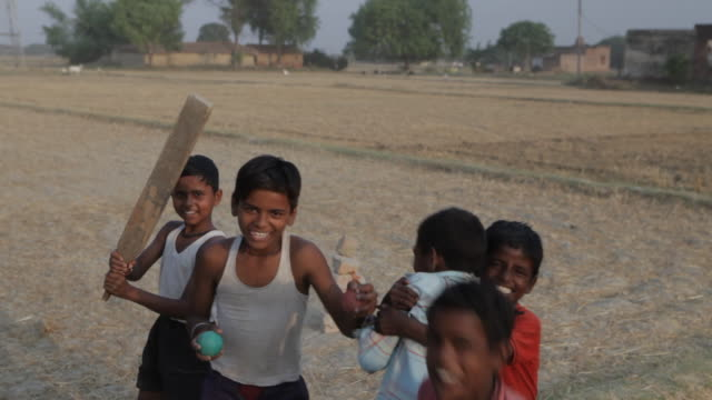 mh young boys playing around holding cricket bat and ball / india - cricket video stock e b–roll