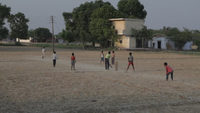 ws young boys playing cricket in dirt field / india - cricket video stock e b–roll