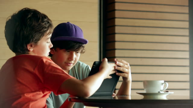 ms young boys playing on a digital tablet in a cafã©. - nur jungen stock-videos und b-roll-filmmaterial