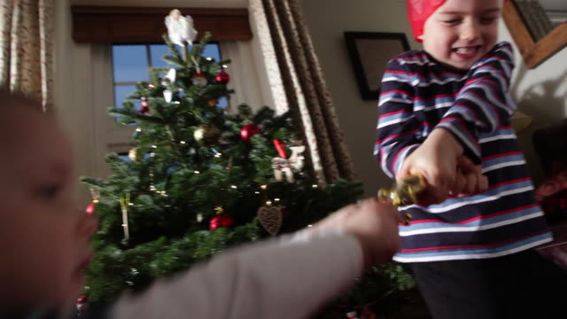 2 young boys pull cracker in front of christmas tree/uk - in front of stock videos & royalty-free footage