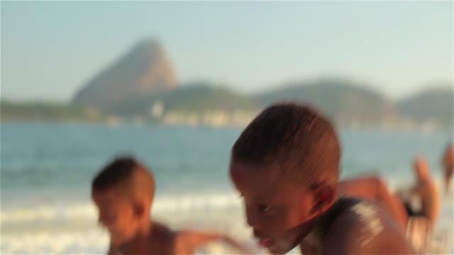 Young boys race across the sand on Brazilian beach