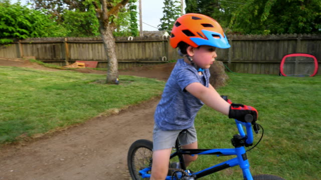 pan young boys riding bmx bikes on backyard dirt track on summer afternoon - bmx cycling stock videos and b-roll footage