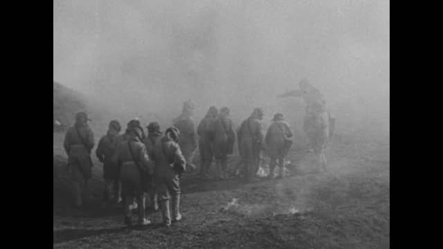 young boys scramble to get in line; tents are behind them / the boys don their gas masks, and an instructor fits a boy; they all wear cloth 'booties'... - air raid video stock e b–roll