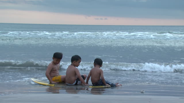 ms young boys sitting at beach, indonesia, bali - jungen stock-videos und b-roll-filmmaterial