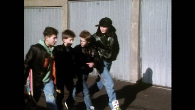 young boys walk along urban road with skateboard; 1989 - cap stock videos & royalty-free footage