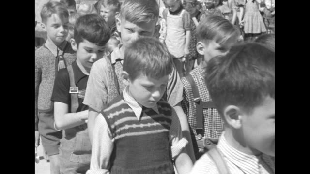 Young boys walk in a group two by two most are wearing lederhosen / MS boys work outside on sewing machine and with hammers making shoes / large...