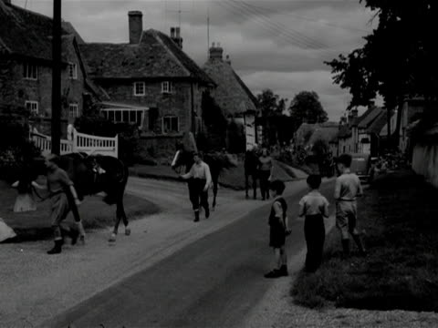 stockvideo's en b-roll-footage met young boys watch stable hands walk horses through the village of east hendred - paardachtigen