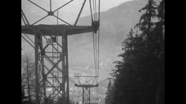 young boys wave from the gondola of an elevated railway / the descent down the side of a mountain the cables a town far below and the station at the... - alto adige video stock e b–roll