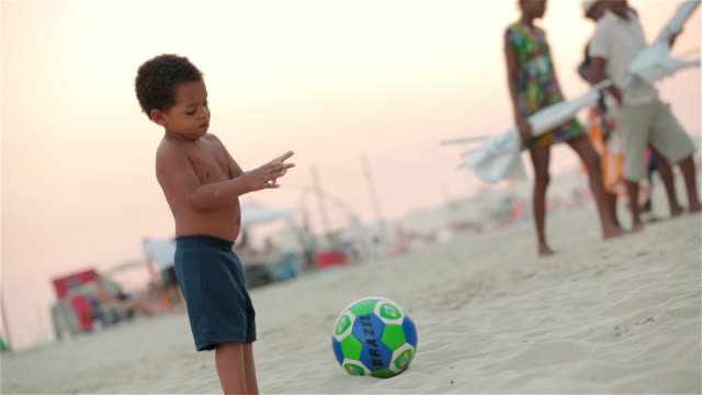Young Brazilian boy brushes sand off hands and rubs belly on Copacabana Beach