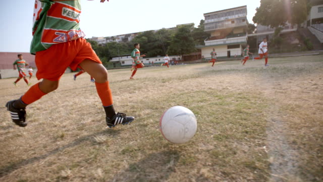 Young Brazilian boy dribbles ball down soccer field in slow motion