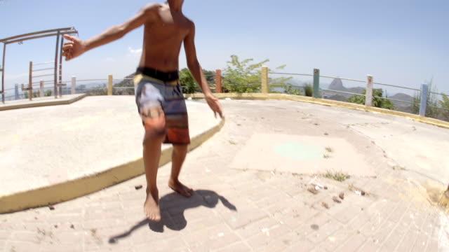 vídeos de stock, filmes e b-roll de young brazilian boy juggles soccer ball in slow motion over rio slum - termo esportivo