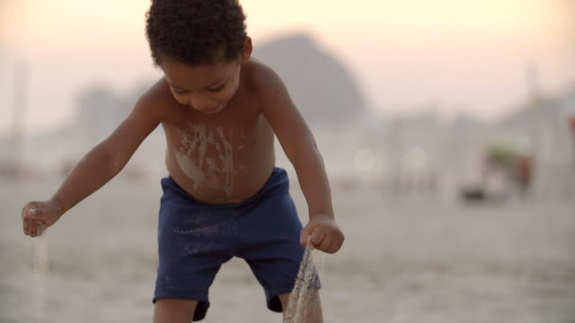 vidéos et rushes de young brazilian boy picks up and drops handfuls of sand on copacabana beach in slow motion - tout petit