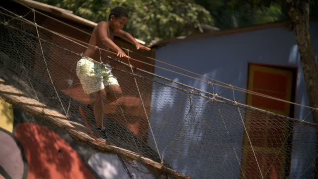 Young Brazilian boy runs across swinging rope bridge in Rio slum