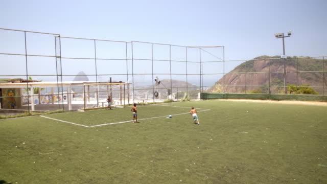 vídeos de stock, filmes e b-roll de young brazilian boy scores goal and celebrates on turf field overlooking rio - termo esportivo