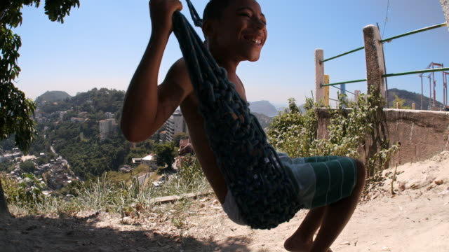 young brazilian boy smiles as he swings from tree overlooking rio de janeiro - bassifondi video stock e b–roll