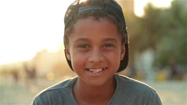 vidéos et rushes de young brazilian boy smiles at camera as sun flares on copacabana beach - casquette
