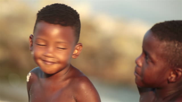 Young Brazilian boy turns and smiles at friend on Botafogo Beach