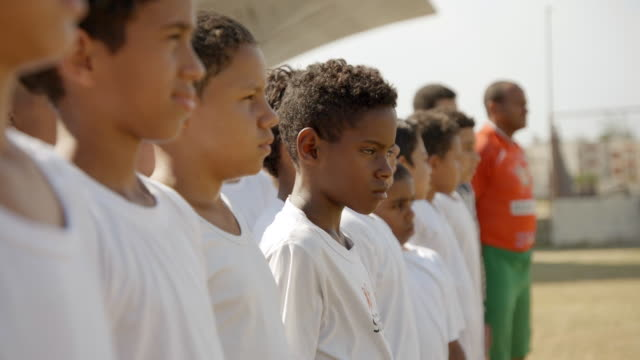 vídeos de stock, filmes e b-roll de young brazilian boy turns to look at camera as youth soccer team stare ahead - orgulho