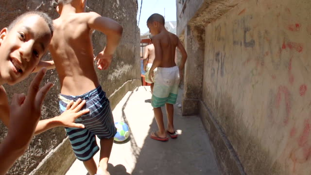 young brazilian boys kick soccer ball through crumbling stone alley, smile and make peace signs at camera - rio de janeiro stock videos & royalty-free footage