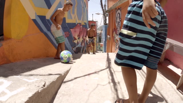 vídeos y material grabado en eventos de stock de young brazilian boys pass soccer ball down alleyway tagged with colorful graffiti and kick ball at camera in slow motion - hispanoamérica